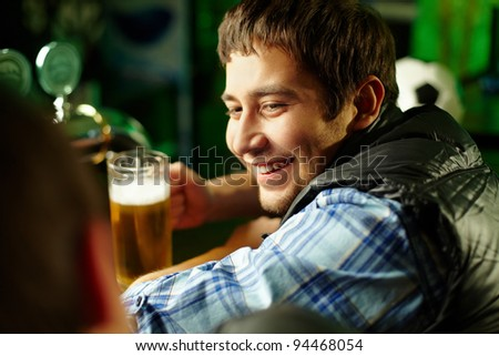 Cheerful male friends spending time together at bar and drinking beer - stock photo
