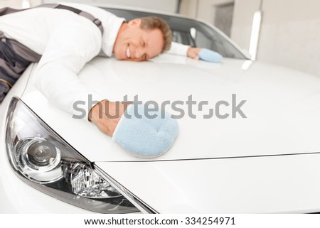 Cheerful male mid aged mechanic is drying a car after washing at car repair shop. He is wearing cloth on his hands and embracing the car with it. The man is smiling with enjoyment - stock photo