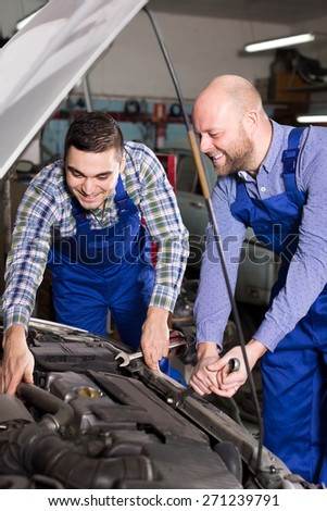 Cheerful male mounting specialists working at auto repair shop.