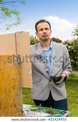 Cheerful male painter working  on a trestle and easel painting with oils and acrylics during an art class - stock photo