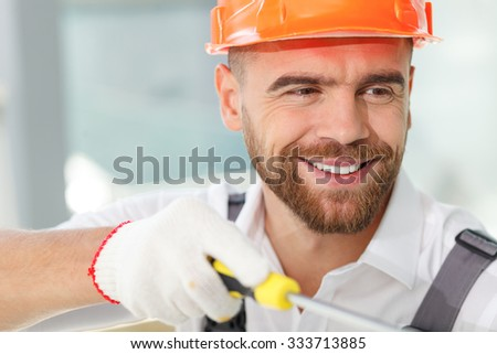 Cheerful male repairman is working at building with screwdriver. He is looking forward with interest and smiling. The man is wearing an orange hardhead - stock photo