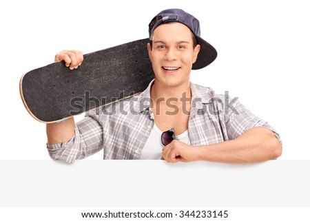 Cheerful male skater holding a skateboard and posing behind a blank billboard isolated on white background - stock photo