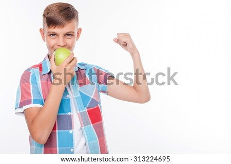 Cheerful male teenager is eating an apple with joy. He is flexing his bicep and showing his strength. The schoolboy is looking at the camera happily. Isolated and copy space in right side - stock photo