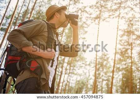 Cheerful male tourist searching for location - stock photo