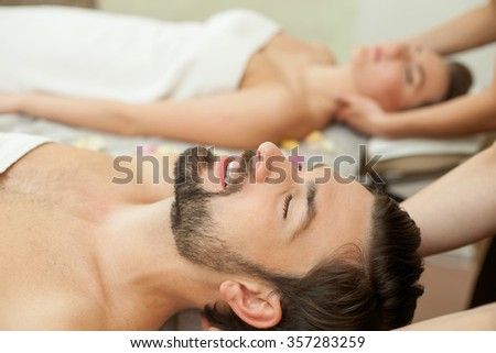Cheerful man and woman are lying and relaxing at spa. The masseuse is massaging their body. The man closed eyes and smiling - stock photo