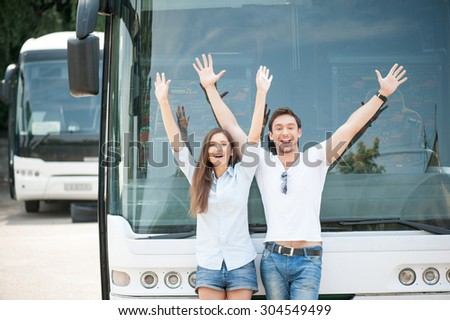 Cheerful man and woman are standing near a bus. They are raising their hands up and smiling. They are enjoying their trip - stock photo