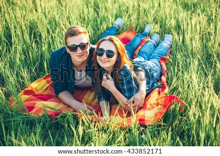 Cheerful man and woman lie on the grass and smiling