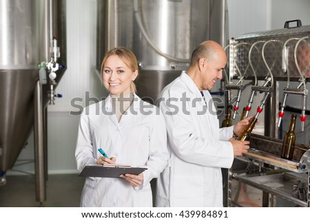 Cheerful man and woman wearing uniform standing among brewery stainless equipment. Focus on woman