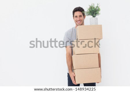Cheerful man carrying boxes because he is moving in a new house - stock photo