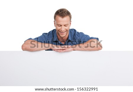 Cheerful man. Cheerful young man leaning at poster and looking at it while isolated on white - stock photo