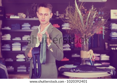 Cheerful man choosing new tie in male cloths store