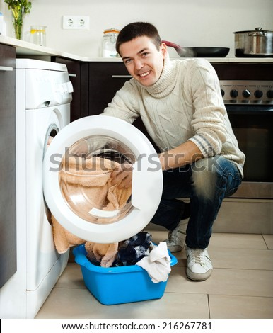 Cheerful man  doing laundry with washing machine at home - stock photo