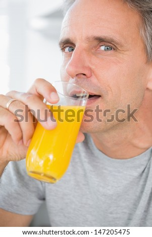 Cheerful man drinking orange juice in kitchen looking at camera