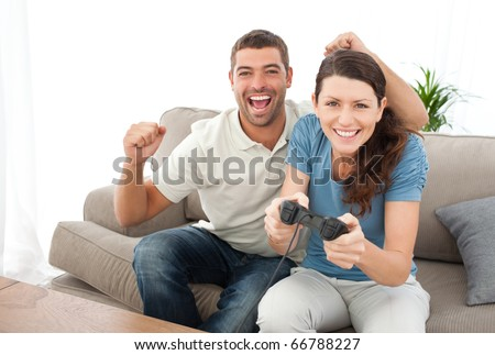 Cheerful man encouraging his girlfriend playing video game at home - stock photo