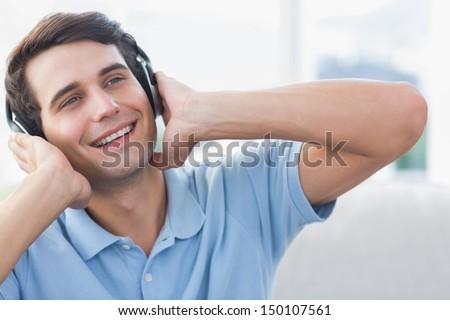 Cheerful man enjoying music with headphones - stock photo