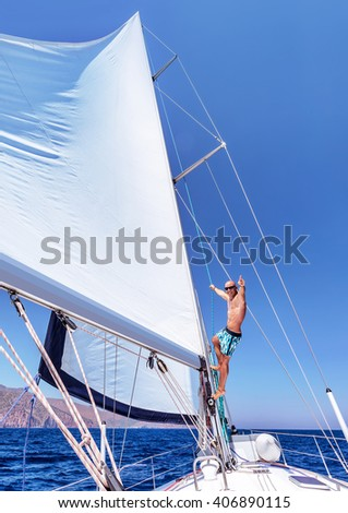 Cheerful man having fun on sailboat, sitting up on the mast of water transport, enjoying active summer vacation, enjoyment and happiness concept - stock photo