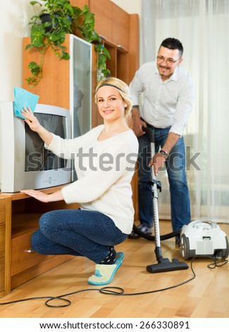 Cheerful man helping his smiling blonde wife cleaning the room. Focus on woman