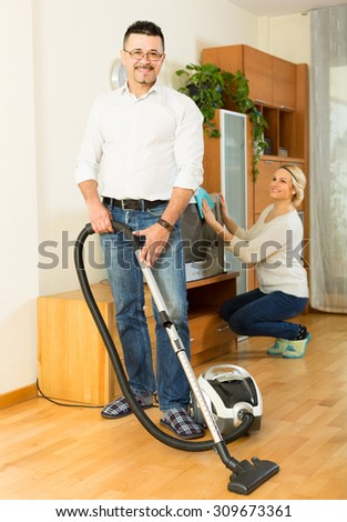 Cheerful man helping his young blonde wife cleaning the room at home - stock photo