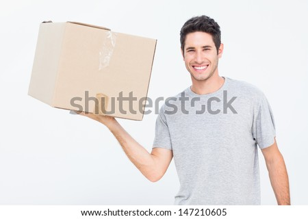 Cheerful man holding a box with one hand - stock photo