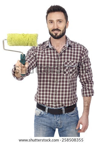 Cheerful man holding a paint roller and looking at camera - stock photo