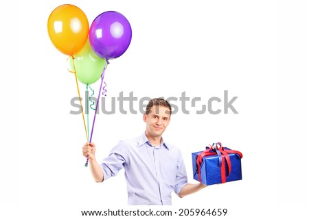 Cheerful man holding balloons and a present isolated on white background