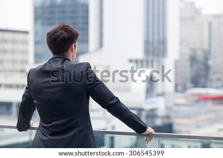 Cheerful man in suit is enjoying the view of the city from a balcony of his office. He is standing and relaxing. Focus on his back. Copy space in right side - stock photo