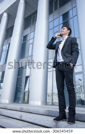 Cheerful man in suit is talking on the telephone with his business partner. He is standing on steps near his office and smiling. The man is putting his arm in a pocket. Copy space in left side - stock photo