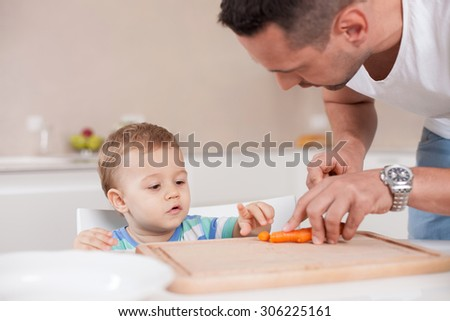 Cheerful man is cutting a carrot for his sun. She is standing near a boy and looking at him with love. The toddler is sitting at the table and looking at a vegetable with interest - stock photo