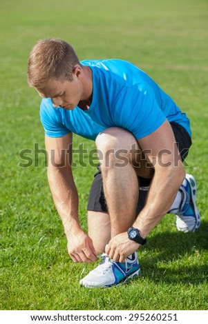 Cheerful man is kneeing and tying his shoelaces on grass. He is looking at it with attention - stock photo