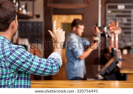 Cheerful man is ordering beer in bar. He is sitting at counter and gesturing to barman. The worker is standing and pouring taping beer carefully - stock photo