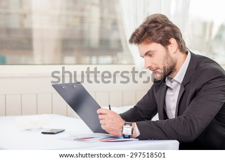 Cheerful man is reading demands of a new project with concentration. He is looking at the folder of documents seriously. The man is sitting at the table. Copy space in left side - stock photo