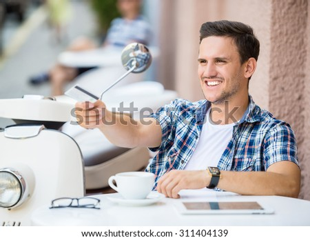 Cheerful man is relaxing in cafe, drinking coffee and giving credit card. - stock photo