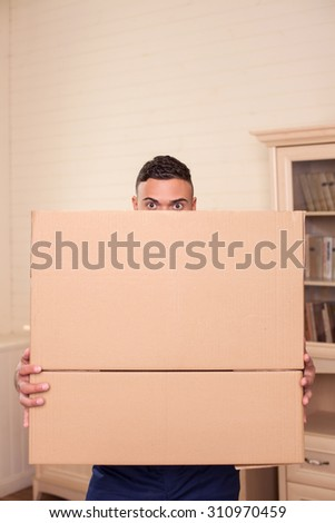 Cheerful man is standing and holding cardboard boxes. His eyes are only visible. The man is looking forward with interest - stock photo