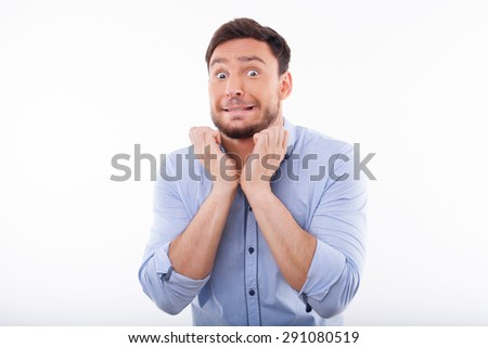 Cheerful man is very scared. He is gritting the teeth and raising his hands to the neck. Isolated on a white background and there is copy space in the left side - stock photo