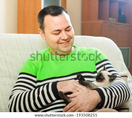Cheerful man on  couch with  little pet - stock photo