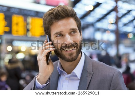 Cheerful man on the mobile phone in hall station in front of Board schedules - stock photo