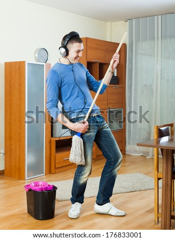 Cheerful man playing with mop in living room