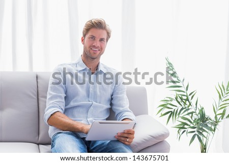 Cheerful man using a tablet pc sat on a couch in the living room - stock photo