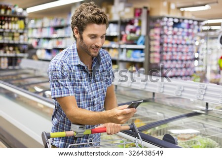 Cheerful man using app mobile phone in store - stock photo