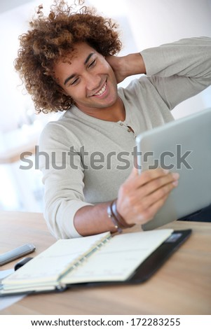 Cheerful man using digital tablet in home office - stock photo