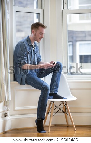 Cheerful Man using his phone at home in the lounge. - stock photo