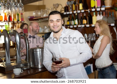 Cheerful man waiting for table in restaurant and drinking wine at tavern - stock photo