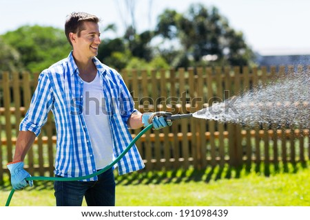 cheerful man watering home garden - stock photo