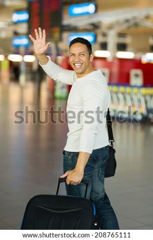 cheerful man waving goodbye at airport - stock photo