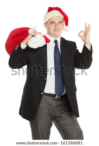Cheerful man wearing a Santas' hat is standing ok sign and with christmas bag full of presents isolated on a white background