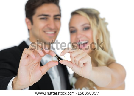 Cheerful married couple showing their wedding rings on white background - stock photo