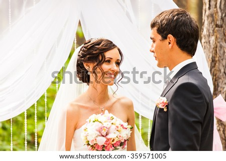 Cheerful married couple standing near the wedding arch - stock photo