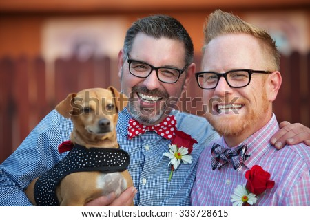 Cheerful married gay couple outdoors with dog - stock photo
