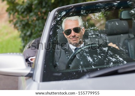 Cheerful mature businessman driving classy cabriolet on sunny day - stock photo