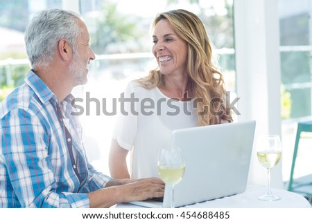 Cheerful mature couple by table in restaurant - stock photo